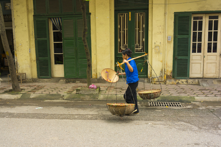 str: Hanoi, Vietnam - April 13, 2014: Unidentified vendor goes home with the empty baskets over old house on Hanoi str, Vietnam
