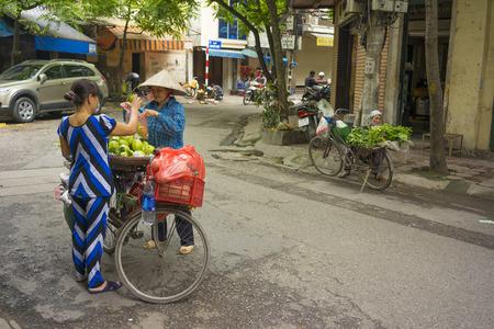 sidewalk sale: Hanoi, Vietnam - April 13, 2014: Unidentified food vendor sells fruits carried by bike to a woman on Hanoi street, Vietnam Editorial