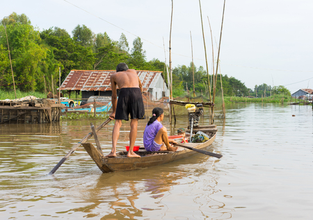 An Giang, Vietnam - Nov 29, 2014: A family moving by rowing boat, the most common transportation mean of rural people in Mekong delta, southern Vietnam Editorial