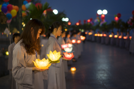 Hanoi, Vietnam - Oct 10, 2014: Buddhists hold flower garlands and colored lanterns for celebrating Buddhas birthday organised at Tran Quoc temple