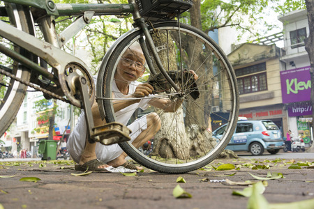 str: Hanoi, Vietnam - May 2, 2014: Unidentified old man fixing his bicycle on street side in Phan Dinh Phung str, Hanoi, Vietnam Editorial