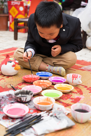 Hanoi, Vietnam - Feb 7, 2015: Schoolboy learn to paint plaster figurine by brush and color ink at Vietnamese lunar new year festival organized at Vinschool, Vinhomes Times City, Minh Khai Editorial