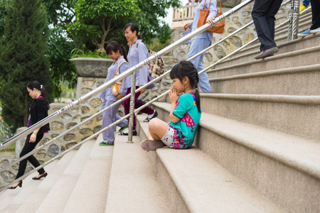 sitting on the ground: Quang Ninh, Vietnam - Mar 22, 2015: Little girl child clasp her hands praying at Cai Bau old temple in Van Don. Some buddhist on brown clothes on background