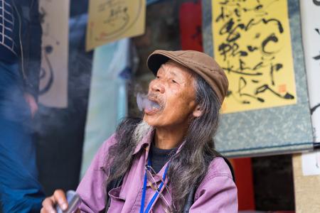 Hanoi, Vietnam - Feb 15, 2015: Vietnamese scholar at lunar new year calligraphy festival organizing at Temple of Literature Van Mieu