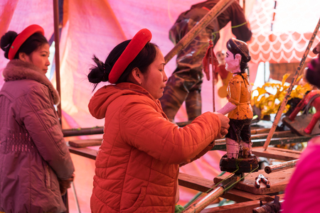 Hanoi, Vietnam - Feb 7, 2015: Female Puppeteer fixes a puppet behide the stage before the show at Vietnamese lunar new year festival organized at Vinschool, Vinhomes Times City, Minh Khai