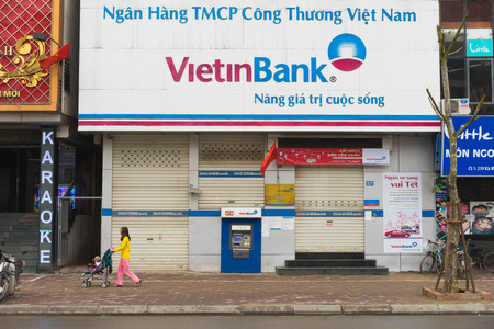 state owned: Hanoi, Vietnam - Mar 15, 2015: Exterior front view of Vietinbank in Xa Dan street. It is one of the four largest State-owned commercial banks of Vietnam. A mother pushes baby carriage on sidewalk