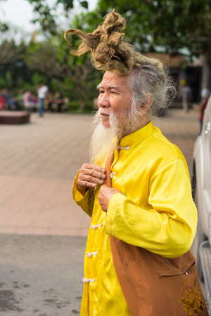 Quang Ninh, Vietnam - Mar 22, 2015: Portrait of old Vietnamese man with very long hair. Hes wearing Buddhist clothes Editorial