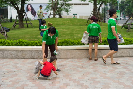 Hanoi, Vietnam - Apr 19, 2015: Family volunteers picking up litter in the park at Times City, a luxury and high class combination of apartment and mega mall retail center in Hanoi