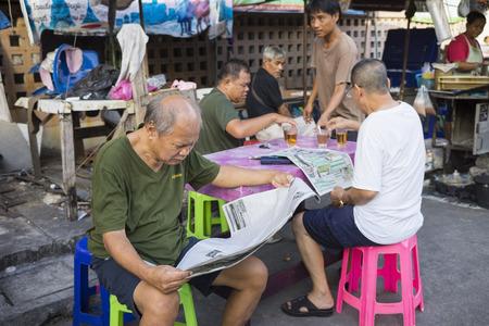 Bangkok, Thailand - June 28, 2015: Old men reading newspaper at a tea stall on Bangkok street