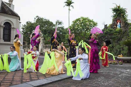 16: Ninh Binh, Vietnam - May 16, 2015: Vietnamese Christian women perform an old traditional dance on flower offering to Mother day at local church Editorial