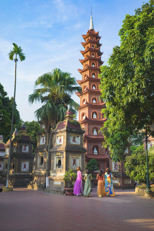 Hanoi, Vietnam - Aug 23, 2015: Yard panoramic view of Tran Quoc temple with women wearing traditional dress Ao Dai visiting the temple. Tran Quoc is the oldest temple in Hanoi Editorial