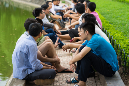 foreigners: Hanoi, Vietnam - July 3, 2016: Group of students learn to speak English with English native foreigners at Hoan Kiem lake. A lot of students choose this way to improve their English speaking skills