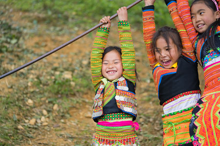Son La, Vietnam - Jan 13, 2016: Ethnic Hmong children in traditional clothes playing on playground during Hmong New Year holiday in Ta Xua village, Bac Yen district Editorial