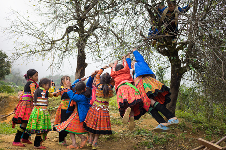 vietnamese ethnicity: Son La, Vietnam - Jan 13, 2016: Ethnic Hmong children in traditional clothes playing on playground during Hmong New Year holiday in Ta Xua village, Bac Yen district Editorial