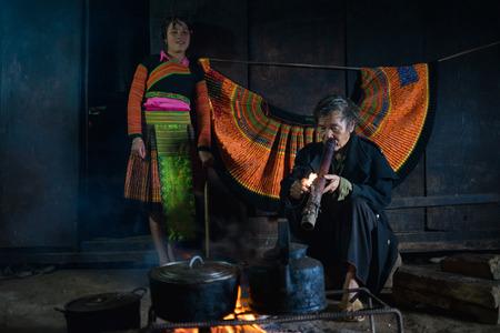 ソンラー son La、ベトナム - 2016 年 1 月 13 日: もん男を吸う火および彼の孫娘の横にある Bac 円地区に彼の家の中 報道画像