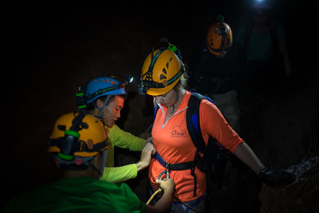 dark cave: Quang Binh, Vietnam - June 20, 2016: People help each others to tighten rock climbing equipments with rope, hook, belt in dark cave in Son Dong, the largest cave in the world