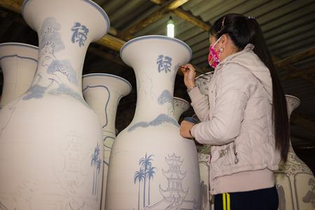 oldest: Hanoi, Vietnam - Jan 2, 2016: Craftsman painting on pottery big decoration vase in Bat Trang ancient ceramic village. Bat Trang village is the oldest and best known pottery village of Vietnam