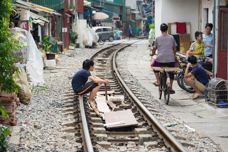 penury: Hanoi, Vietnam - Nov 8, 2015: Children play on no barriers train railway in Hanoi