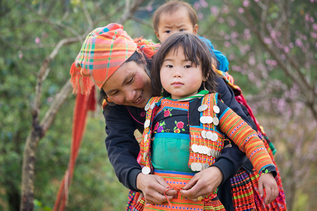 Son La, Vietnam - Jan 13, 2016: Hmong girl child wearing traditional clothes with her mother in Ta Xua village, Bac Yen district