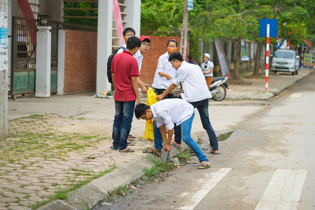 environmentalist: Bac Ninh, Vietnam - Sep 9, 2015: Group of high school students cleaning street in front of their school within the volunteer event for saving environment Editorial