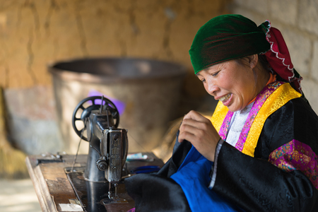 Ha Giang, Vietnam - Feb 14, 2016: Hmong woman making clothes by old sewing machine in front of her house in Dong Van district