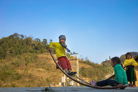 Ha Giang, Vietnam - Feb 14, 2016: Ethnic minority Hmong children play seesaw made of curved metal rod. Most of Hmong households have difficult life with very low income