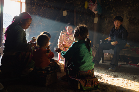 ha giang: Ha Giang, Vietnam - Feb 13, 2016: Hmong ethnic minority family having lunch in their house in Yen Minh district, under sun beam as source of light