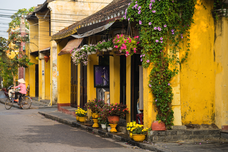 Quang Nam, Vietnam - Apr 2, 2016: Old aged house with yellow wall and flower pots against cycling woman on background. Hoi An is UNESCO site