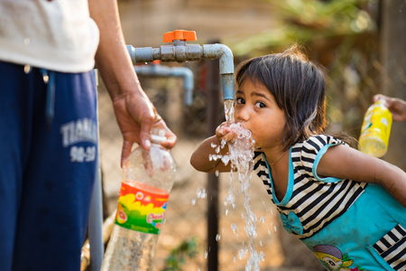 plastic pipe: Kon Tum, Vietnam - Mar 29, 2016: A little girl drink water from outdoor tap which water supplied by drilling well in Central Highland of Vietnam. Fresh water is problem in underdevelopment region