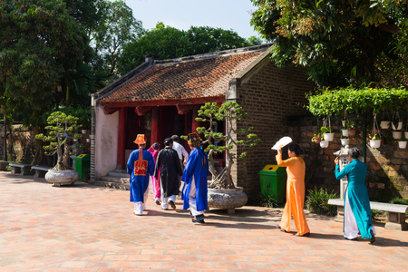 Hanoi, Vietnam - July 24, 2016: Dai Thanh gate to fifth courtyard in Temple of Literature ( Van Mieu ) with people wearing old traditional long dress Ao Dai walking on courtyard
