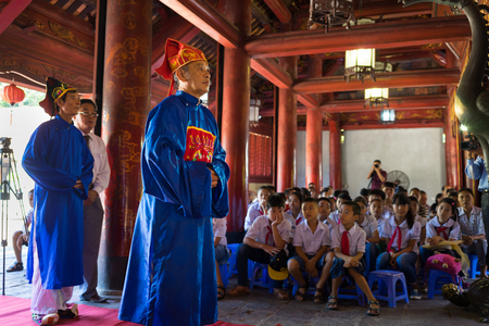 Hanoi, Vietnam - July 24, 2016: Men wearing old feudal government official showing respect at commend celebration for family good pupils organised at Temple of Literature (Van Mieu)