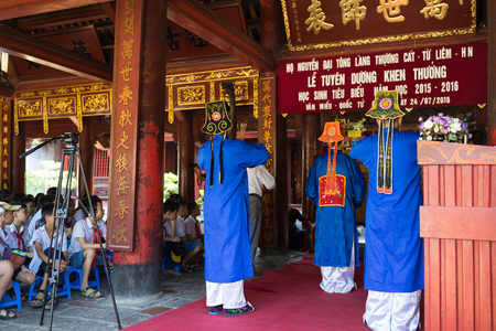 commend: Hanoi, Vietnam - July 24, 2016: Men wearing old feudal government official showing respect at commend celebration for family good pupils organised at Temple of Literature (Van Mieu)