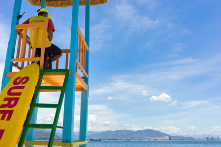 Lifeguard sitting in his chair watching the sea 写真素材