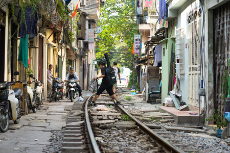Hanoi, Vietnam - Aug 7, 2016: Railway crossing the middle of Hanoi city with crowded houses. A man walking on the rails