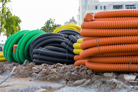 Pile of big industrial plastic corrugated pipes on ground Stock Photo
