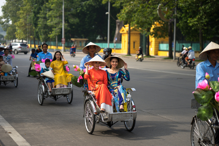 Hanoi, Vietnam - Oct 16, 2016: Vietnamese girl wears traditional long dress Ao Dai going by Cyclo (pedicab) on Hanoi street Editorial