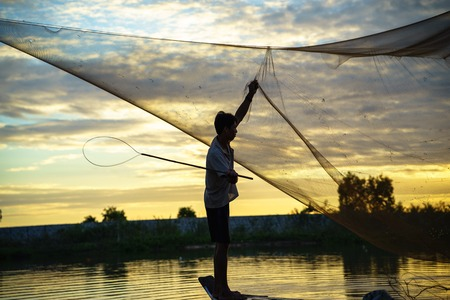 can tho: An Giang, Vietnam - Dec 6, 2016: Fisherman cleaning fishing net on Tha La cultivated field in An Giang province, Mekong delta, South Vietnam