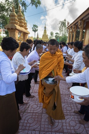 An Giang, Vietnam - Dec 6, 2016: Buddhist monk in south of Vietnam stand in a row waiting people put rice and food offerings in their alms bowl in Chau Doc district
