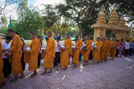 limosna: An Giang, Vietnam - Dec 6, 2016: Buddhist monk in south of Vietnam stand in a row waiting people put rice and food offerings in their alms bowl in Chau Doc district