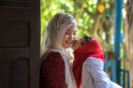 An Giang, Vietnam - Sep 6, 2016: Vietnamese muslim girl wearing traditional red dress playing with her sister in a champa village, Khanh Hoan district, South Vietnam Editorial