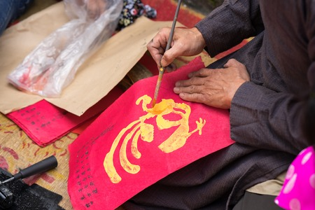 Hanoi, Vietnam - Jun 22, 2017: Old Dong Ho village artist making Dong Ho folk woodcut painting in communal house, Quoc Oai district. Concept of cultural preservation