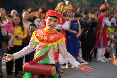 Hanoi, Vietnam - Feb 5, 2017: Men with women dress performing ancient dance called Con Di Danh Bong - Prostitutes beat the drum at spring festival in Trieu Khuc village. Editorial
