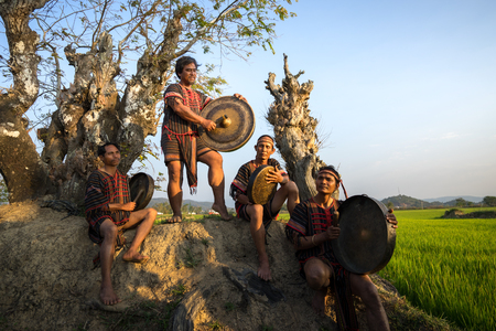 Daklak, Vietnam - Mar 9, 2017: Ede ethnic minority people perform traditional gong and drum dance in their festival under big tree in sunset period. 報道画像