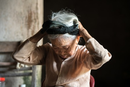 difficult lives: Ninh Binh, Vietnam - Apr 10, 2017: Portrait of an elderly woman with white hair living alone in the very old and poor house.