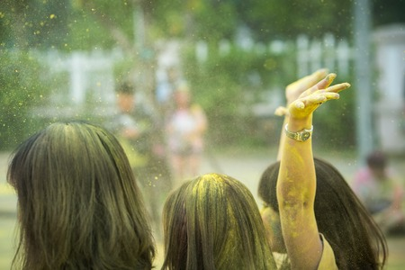 Hand of a girl raising up with colorful hair heads closeup at an color run event. Soft focus. Stock Photo