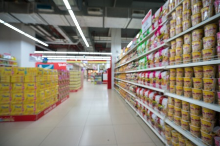 Supermarket blurred background with colorful shelves and unrecognizable customers