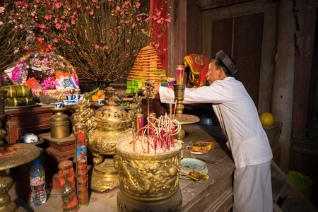 Hanoi, Vietnam - Jun 22, 2017: Old man preparing worship offerings on altar on holiday in communal house at So village, Quoc Oai district.