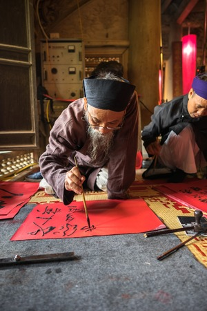 Hanoi, Vietnam - Jun 22, 2017: Scholar writes Chinese calligraphy characters in communal house at So village, Quoc Oai district. Calligraphy giving is a popular tradition during Tet holiday Publikacyjne