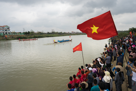 Bac Ninh, Vietnam - Feb 7, 2017: Cheering audiences at traditional boat racing spring festival on Cau river, Bac Ninh province