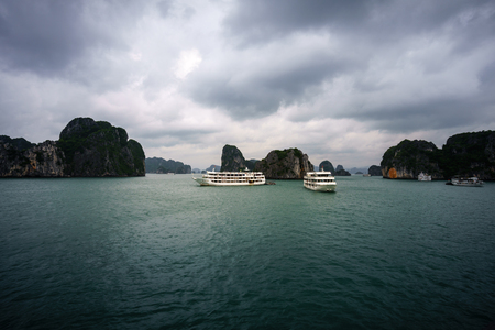 Halong bay at sunset with tourist cruise ships and rocky islands. Popular landmark, famous destination of Vietnam Stock Photo